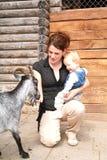 Donna con il bambino che picchietta la capra allo zoo Fotografia Stock