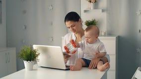 Donna con il bambino ed il computer portatile stock footage