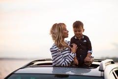Donna con il bambino sul tetto dell'automobile Fotografie Stock Libere da Diritti