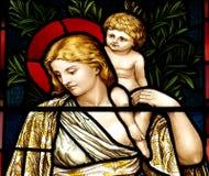 Donna con il bambino in vetro macchiato fotografia stock libera da diritti