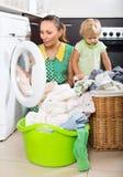 Donna con il bambino vicino alla lavatrice Fotografia Stock