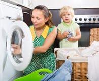 Donna con il bambino vicino alla lavatrice Fotografia Stock Libera da Diritti