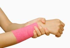 Donna con il banage rosa che ha dolore in suo polso Fotografie Stock