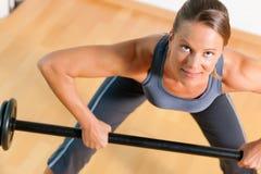 Donna con il barbell in ginnastica Immagini Stock
