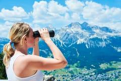 Donna con il binocolo che guarda le montagne fotografie stock