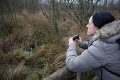 Donna con il birdwatching del binocolo Fotografie Stock Libere da Diritti
