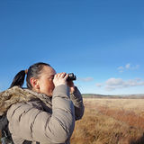 Donna con il birdwatching del binocolo Fotografia Stock Libera da Diritti