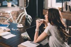 Donna con il caffè bevente del computer portatile Fotografia Stock