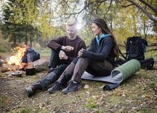 Donna con il caffè della macinazione dell'uomo durante il campeggio nella foresta immagini stock
