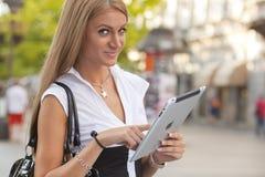 Donna con il calcolatore del ridurre in pani del iPad sulla via urbana Immagine Stock