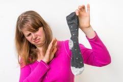 Donna con il calzino puzzolente del suo marito Fotografia Stock