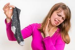 Donna con il calzino puzzolente del suo marito Fotografie Stock