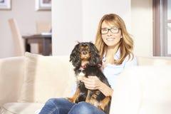 Donna con il cane di animale domestico a casa fotografia stock libera da diritti