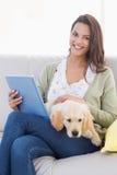 Donna con il cane facendo uso del computer della compressa sul sofà Immagini Stock Libere da Diritti