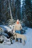 Donna con il cane nella foresta di inverno Fotografia Stock