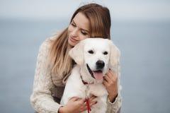 Donna con il cane sulla riva di mare immagine stock