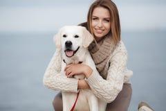 Donna con il cane sulla riva di mare fotografie stock libere da diritti