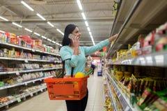 Donna con il canestro dell'alimento e smartphone al deposito Fotografia Stock Libera da Diritti