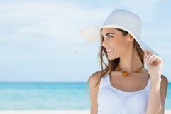 Donna con il cappellino da sole alla spiaggia Fotografia Stock