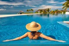 Donna con il cappello allo stagno della spiaggia in Maldive fotografia stock