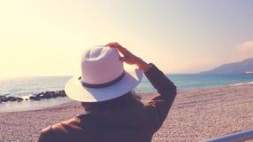 Donna con il cappello che esamina il mare archivi video