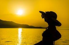 Donna con il cappello che gode sulla spiaggia fotografie stock