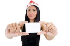 Donna con il cappello del Babbo Natale ed il biglietto da visita in bianco Immagini Stock Libere da Diritti