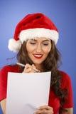 Donna con il cappello di Natale con una lista Fotografia Stock Libera da Diritti