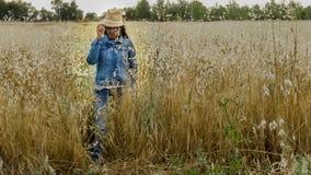 Donna con il cappello in un giacimento di grano, donna felice immagini stock