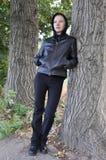 Donna con il cappuccio nero degli alberi Immagine Stock