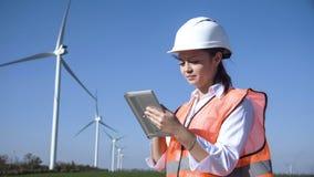 Donna con il casco contro il generatore eolico fotografia stock