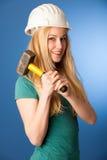 Donna con il casco del costruttore e martello felice di fare lavoro duro Fotografia Stock