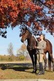 Donna con il cavallo di Brown nella caduta Fotografie Stock