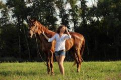 Donna con il cavallo di razza di dressage che cammina in un campo Fotografia Stock