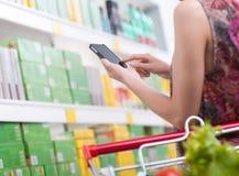 Donna con il cellulare al supermercato Immagine Stock