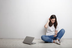 Donna con il cellulare e le cuffie che si siedono vicino ad una parete bianca Fotografie Stock Libere da Diritti