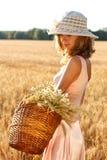 Donna con il cestino pieno del frumento maturo delle orecchie Fotografie Stock Libere da Diritti
