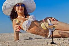 Donna con il cocktail che si rilassa sulla spiaggia Fotografia Stock
