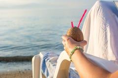 Donna con il cocktail della noce di cocco alla spiaggia Immagini Stock Libere da Diritti