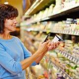 Donna con il codice a barre di esame dello smartphone in supermercato Fotografie Stock