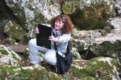 Donna con il computer della compressa nelle montagne Fotografie Stock