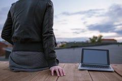 Donna con il computer portatile in bianco sul contesto del cielo Fotografia Stock