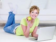 Donna con il computer portatile che mangia mela Immagini Stock