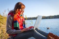 Donna con il computer portatile che scrive vicino al lago Fotografie Stock Libere da Diritti
