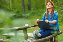 Donna con il computer portatile che si siede sul banco del giardino Fotografia Stock