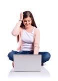 Donna con il computer portatile che si siede sul pavimento, colpo dello studio, isolato Fotografie Stock Libere da Diritti