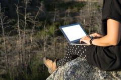 Donna con il computer portatile che si siede sull'orlo di una roccia Fotografia Stock Libera da Diritti