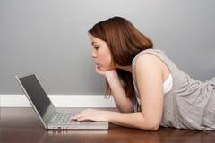 Donna con il computer portatile che si trova sul pavimento Fotografia Stock