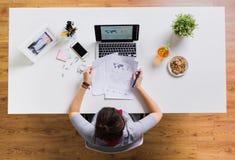 Donna con il computer portatile e le carte alla tavola dell'ufficio fotografia stock libera da diritti