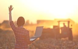 Donna con il computer portatile ed il trattore Fotografie Stock
